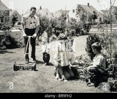 1950ER JAHRE FAMILIE IN HINTERHOF PAPA UND KLEINKIND SCHNEIDEN GRASS, MUTTER UND KINDER IM GARTEN - Stockfoto