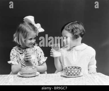 1930ER JAHREN ZWEI LÄCHELNDE MÄDCHEN TRINKEN MILCH SCHÜSSEL MÜSLI ESSEN LACHEN REDEN - Stockfoto