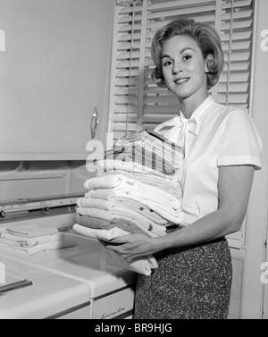 1960ER JAHREN LÄCHELNDE FRAU MIT GEFALTETEN WÄSCHE BLICK IN DIE KAMERA - Stockfoto