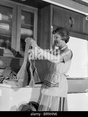 1960ER JAHREN FRAU FALTUNG WÄSCHE HANDTÜCHER ON TROCKNER IN KÜCHE - Stockfoto