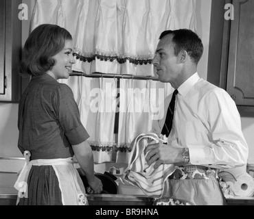 1960ER JAHRE MANN FRAU WASCHEN GESCHIRR SPÜLE - Stockfoto