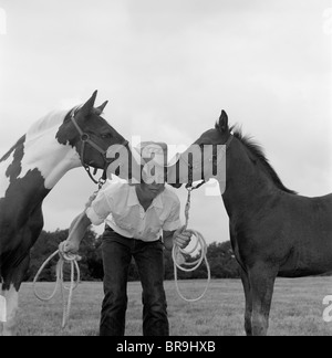 1960ER JAHRE JUNGE COWBOY HUT HÄLT SEILE ZÜGEL HARNESS HALTER VON 2 PFERDEN EIN AUF BEIDEN SEITEN DES GESICHTES - Stockfoto