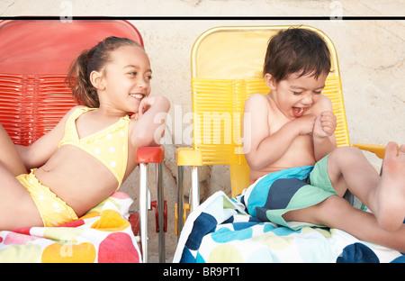 Kinder in Badeanzügen auf Liegestühlen - Stockfoto
