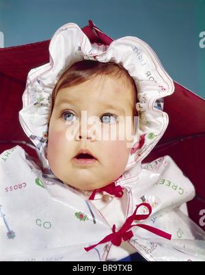 1960ER JAHRE BABY TRAGEN REGENMANTEL UND HUT - Stockfoto