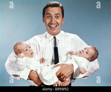 1960ER JAHREN LÄCHELND MANN VATER BLICK AUF KAMERA HOLDING TWIN BABYS KLEINKINDER - Stockfoto