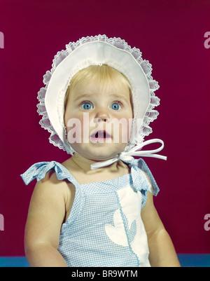 1960ER JAHRE BLONDE BABY BLAU AUGEN TRAGEN ZERZAUSTE MÜTZE GESICHTSAUSDRUCK DES STAUNENS BLICK IN DIE KAMERA - Stockfoto