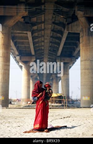 Mutter in einen roten Sari gekleidet mit einem Kind in ihren Armen unter einer Brücke in Allahabad Indien. - Stockfoto