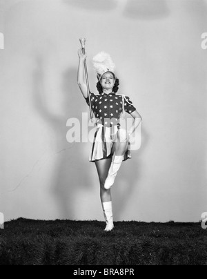 1940ER JAHRE MAJORETTE POSIERT MIT SCHLAGSTOCK MIT BLICK NACH VORNE TRAGEN PATRIOTISCHEN STARS AND STRIPES EINHEITLICHE - Stockfoto