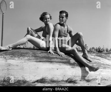 1930ER JAHREN PAAR MANN FRAU LÄCHELND TRAGEN BADEANZÜGE SITZEN RÜCKEN AN RÜCKEN AUF UMGESTÜRZTEN HOLZBOOT - Stockfoto