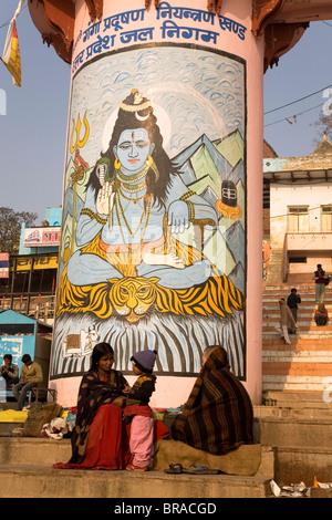 Indian vor eine Säule lackiert mit dem hinduistischen Gott Shiva auf die Ghats von Varanasi, Uttar Pradesh, Indien - Stockfoto