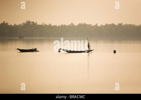 Ein Mann steht auf einem Boot in den Sunderbans (Sundarbans) National Park, UNESCO-Weltkulturerbe, West Bengalen, - Stockfoto
