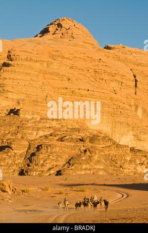 Kamel-Karawane in die atemberaubende Wüstenlandschaft von Wadi Rum, Jordanien, Naher Osten - Stockfoto