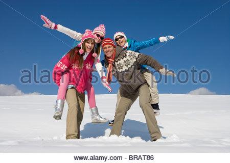 Eltern, Kinder Huckepack fahren im stehen im Schnee - Stockfoto