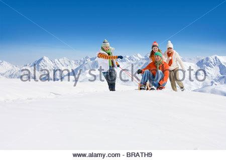 Sohn Vater auf Schlitten durch Schnee als Mutter und Tochter Push ziehen - Stockfoto