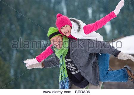 Mann mit Freundin Huckepack Reiten im Schnee - Stockfoto