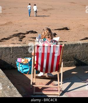 eine junge Frau sitzt in einem Liegestuhl am Summerleaze Beach, Bude, cornwall - Stockfoto