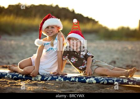 Jungen und Mädchen auf Urlaub Surfbrett - Stockfoto