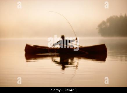 Mann im Kanu an einem nebeligen Tag Angeln - Stockfoto