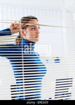 Geschäftsfrau sucht durch Jalousien - Stockfoto