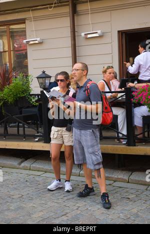 Touristen-paar auf der Suche auf Karte und Reiseführer Stortorget Platz Gamla Stan Altstadt Stockholm Schweden Europa - Stockfoto