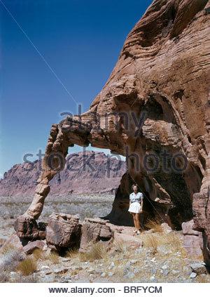Neben einer großen, erodierten Felsformation steht eine Frau. - Stockfoto