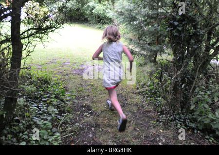 Ein 8 Jahre altes Mädchen rennt in ein Feld - Stockfoto