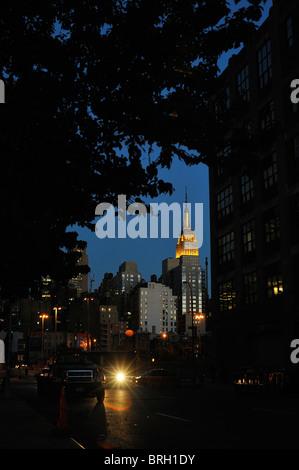 New Yorker Wahrzeichen der Empire State Building gold Lichter oben und Spire nachts beleuchtet gesehen, umrahmt - Stockfoto