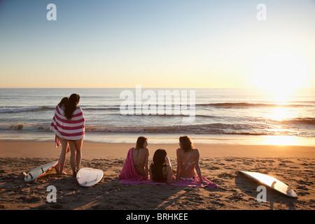 Rückansicht der jungen Frauen mit Surfbrettern am Strand bei Sonnenuntergang, Zuma Beach, Kalifornien, USA - Stockfoto