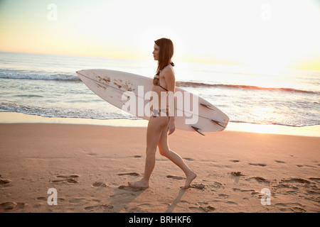 Junge Frau mit Surfbrett und Wandern am Strand, Zuma Beach, Kalifornien, USA - Stockfoto