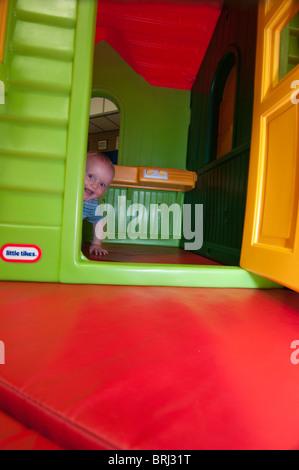Baby spähen Runde spielen Haustür - Stockfoto