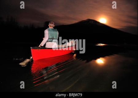 Ein Mann in einem roten Boot Kanu fahren nachts an einem Bergsee in Oregon. - Stockfoto