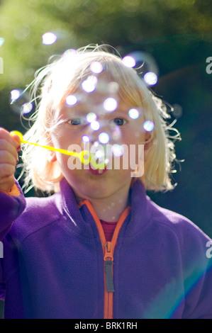junges Kind Mädchen bläst Seifenblasen im Sonnenschein - Stockfoto