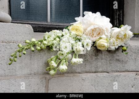 Reihe von weißen Schnittblumen einschließlich Pfingstrose, Rittersporn und cremefarbenen Rosen aufgegeben am Fensterbrett - Stockfoto