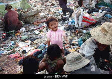 Ein junges Mädchen, die in Armut lebenden Menschen ist lächelnd, als ihre Familie wiederverwertbaren Müll in eine - Stockfoto