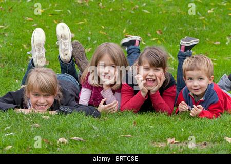Porträt von vier kleinen Kindern liegen auf einer Wiese in die Kamera schaut - Stockfoto