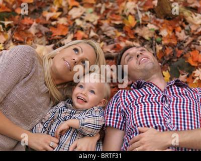 Glücklich lächelnde junge Eltern und ein zwei Jahre altes Mädchen auf bunten umgestürzten Baum liegen in der herbstlichen - Stockfoto