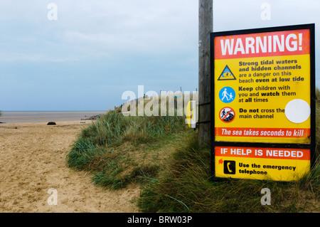 Ein Schild am Eingang zum Brancaster Beach in North Norfolk warnt vor den Gefahren von starken Gezeitenströmungen - Stockfoto