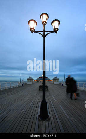 Cromer Pier an der Küste von Norfolk am frühen Abend mit ein paar walking. - Stockfoto