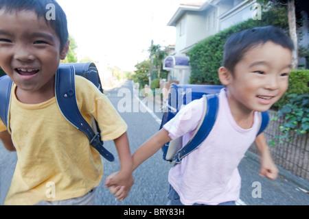 Jungen halten sich an den Händen und laufen, Präfektur Tokio, Honshu, Japan
