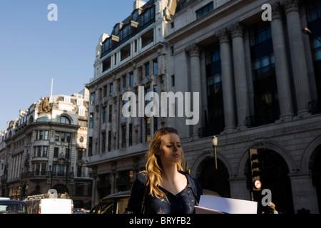 Eine junge Frau ist in ihren Gedanken verloren, bei einem Spaziergang entlang Piccadilly. - Stockfoto