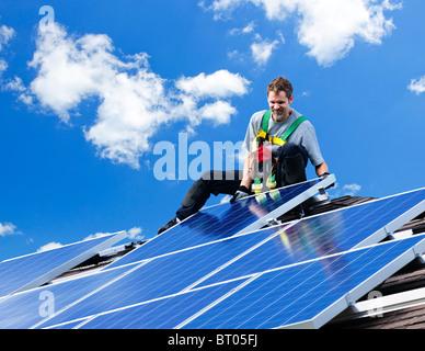 Arbeiter, die Installation von alternativen Energien Photovoltaik-Solarzellen auf Dach - Stockfoto