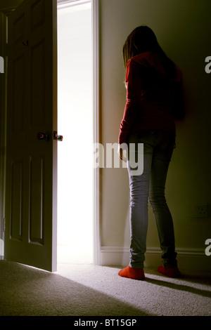 Junge Frau in einem dunklen Schlafzimmerwand als Lichtströme in gelehnt. - Stockfoto