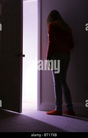 Junge Frau lehnt sich an die Wand eines dunklen Raumes, offene Tür mit Licht, das - Stockfoto