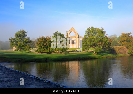 Bolton Priory und Stepping Stones River Wharfe im Herbst Nebel, Bolton Abbey, Yorkshire Dales National Park, North - Stockfoto