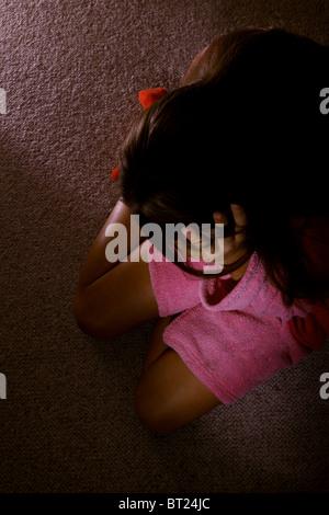 Mädchen tragen einen Morgenmantel, sitzt auf einem Teppichboden mit dem Kopf in die Hände. - Stockfoto