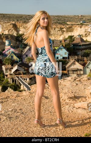 attraktive blonde Frau in kurzem Kleid ihr Fuß verstaucht ...  attraktive blon...