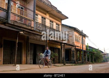Eine Frau reitet ein Fahrrad vorbei an alten Gebäuden auf einem Feldweg in Champasak, Laos. - Stockfoto