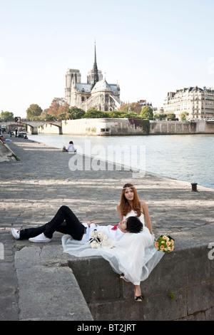 ziemlich Asian Braut sitzt Gacefully mit des Bräutigams Kopf in ihrem Schoß am Quai De La Tournelle Kulisse von - Stockfoto