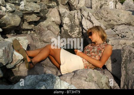 Eine schöne junge blonde Frau schreiben, lesen, Sonnenbaden auf den Felsen. Mädchen, Bikini, Sonnenbrille, Flip - Stockfoto