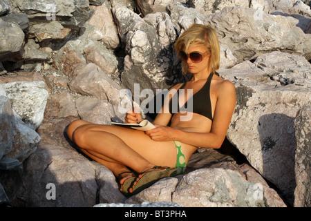 Eine schöne junge blonde Frau schreiben & sitzen auf den Felsen Sonne gesegnet. Mädchen, Bikini, Sonnenbrille, Flip - Stockfoto